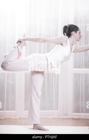 Young woman practicing yoga (Modellfreigabe) - Stock Photo