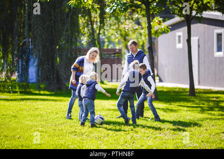 The theme family outdoor activities. big friendly Caucasian family of six mom dad and four children playing football, running with the ball on lawn, g - Stock Photo