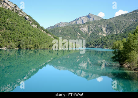 Reflections of the Surrounding Mountains in Chaudanne Lake or Lac de Chaudanne near Castellane in the Verdon regional Park Alpes-de-Haute-Provence - Stock Photo