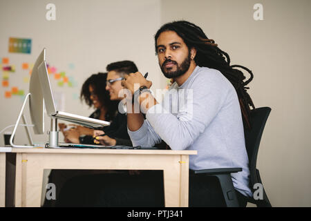 Businessman sitting at his desk with a laptop and digital writing pad on the table with colleagues. Business people working in office sitting at their - Stock Photo