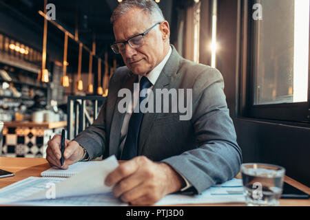 Senior businessman sitting at cafe table reading a document and making notes. Mature man in suit working on new project budget. - Stock Photo