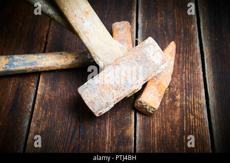 Close up of tree old used hammer on a rustic wooden background. Selective focus - Stock Photo