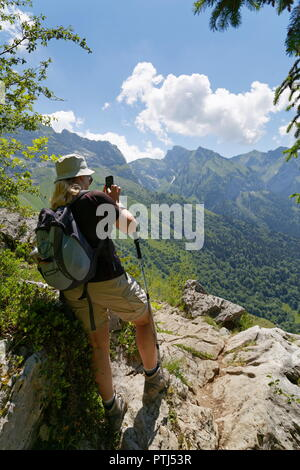 Female hiker taking a picture on her phone at a look out point from a trail around Col de la Forclaz looking towards La Tourneete France - Stock Photo