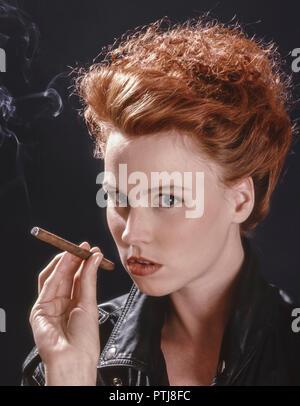 Rotharige junge Frau raucht ein Zigarillo (Modellfreigabe) - Stock Photo