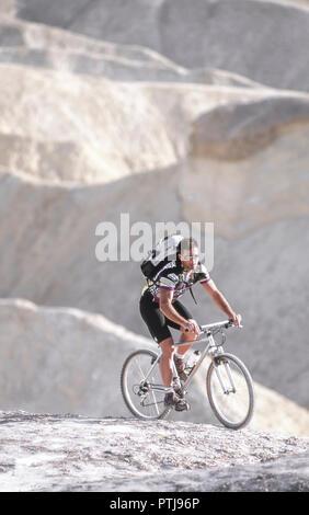 Mann unterwegs mit dem Mountainbik in oedem gelaende (Modellfreigabe) - Stock Photo