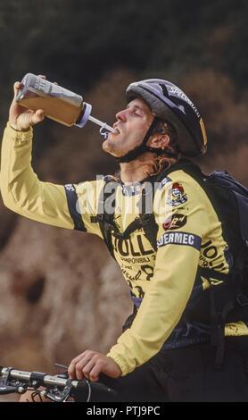 Mann unterwegs mit dem Mountainbike trinkt aus einer Plastikflasche (Modellfreigabe) - Stock Photo