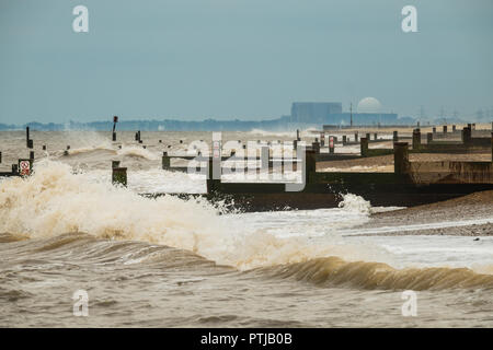 Waves break on the beach and groynes at Southwold with Sizewell nuclear power station in the distance. - Stock Photo