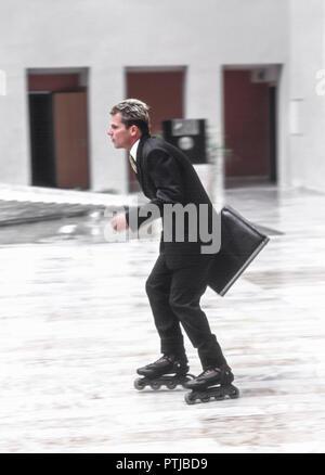Karrieremann in Anzug mit Aktenkoffer, faehrt mit Inlineskates, Symbol Erfolg und Dynamik (Modellfreigabe) - Stock Photo