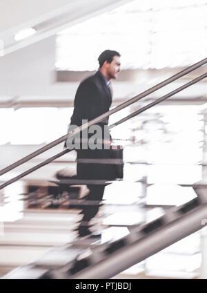 Karrieremann in Anzug mit Aktenkoffer laeuft eine Treppe hinauf (Modellfreigabe) - Stock Photo