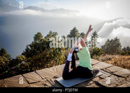 A women in a yoga pose during sunrise at Poon Hill in Nepal. - Stock Photo