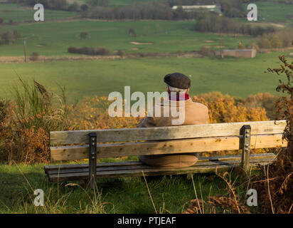 An elderly man wearing a cap is sitting on a wooden bench looking over the countryside. - Stock Photo