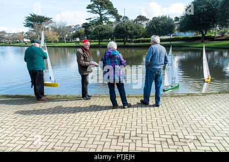 Members of the Newquay Model yacht Club at Trenance Boating Lake preparing to start a race in Newquay in Cornwall. - Stock Photo