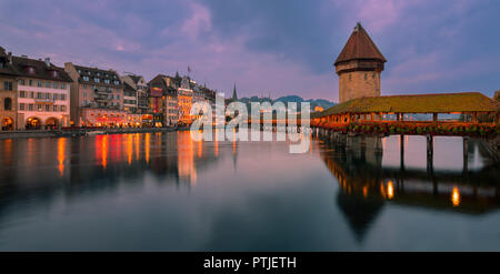 The Kapellbrücke (Chapel Bridge) is a covered wooden footbridge spanning diagonally across the Reuss in the city of Lucerne in central Switzerland. - Stock Photo