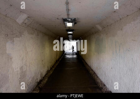 A figure walking through a dark and gloomy underpass in Truro City centre in Cornwall. - Stock Photo
