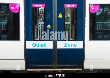 The closed doors of a C2C train stationary in a train station. - Stock Photo