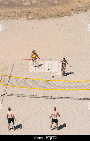 Young people playing beach volleyball on Tolcarne Beach in Newquay in Cornwall. - Stock Photo