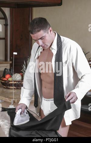 Mann in Hemd und in Unterhose buegelt seine Hose, Frei f?r Werbung (Modellfreigabe) Stock Photo