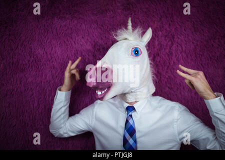 Freaky young man in comical mask stands on the purple background. Portrait of unusual manager. Funny unicorn in shirt and tie is showing rock gesture. - Stock Photo