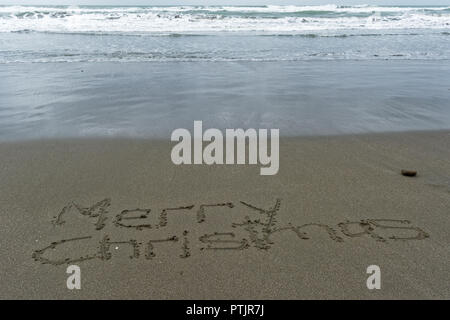Merry Christmas written in the sand on the beach - Stock Photo