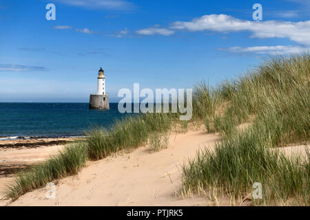 Rattray Head Lighthouse in the North Sea at Buchan Aberdeenshire Scotland with sea grass on sand dunes and sandy beach - Stock Photo