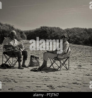 Am Strand Langeoog. Germany Deutschland.  Old couple sitting on their folding chairs on the beach.  They're bought a day bag and Newspaper so they can enjoy sitting in the sun all day.  This is a street photography style photograph peoples' observing culture and lifestyle.  This photograph is timeless being in black & white, monochrome, as is the couple's attire.  It's a clear sunny day.  The beach is pure sand that leads back to sand dunes with a through path that leads back into Langeoog. - Stock Photo