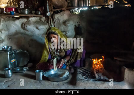 Preparation of Chapati in a village of Rajasthan - Stock Photo