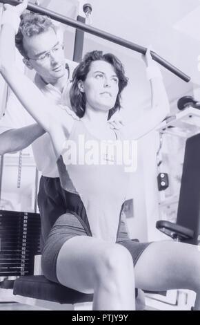 Frau, Fitnesscenter, Trainer, Fitnesstrainer, Mann, , Trainingsgeraet, S/w, Aktivitaet, Erwachsene, Fitness, Fitnessgeraet, Gesundheit, Kraft, Kraefti - Stock Photo