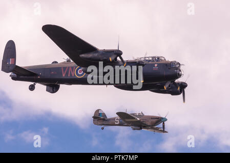 WWII Royal Air Force Avro Lancaster bomber escorted by Hawker Hurricane fighter at the IWM Duxford Air Show. - Stock Photo