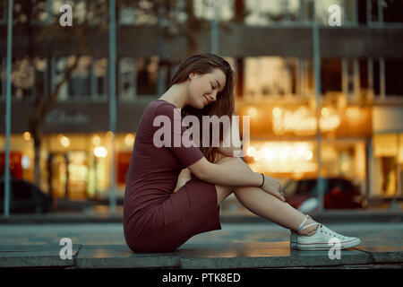 Side view of pretty young woman with fairytale face features enjoy city view with lights in the background. Beautiful urban girl portrait wearing dres - Stock Photo
