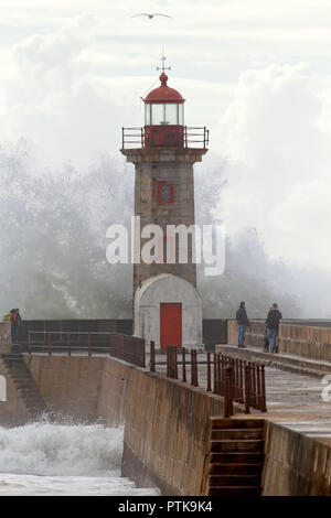 Porto, Portugal - January 25, 2016: People watching dangerous sea waves breaking against old granite pier and lighthoouse, Portugal - Stock Photo