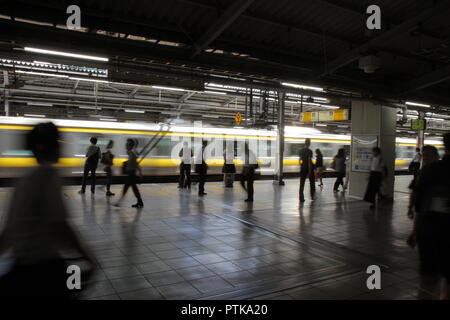 Passengers in a train station : A yellow train passes rapidly through a railway station, in front of passengers waiting and walking on the platform. - Stock Photo