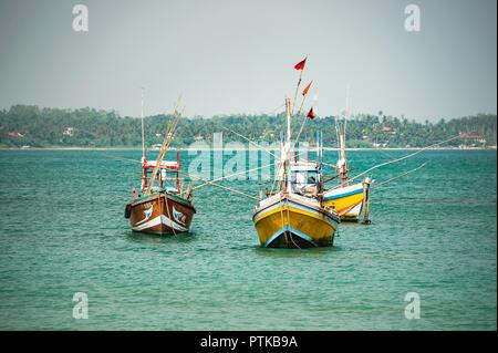 Traditional wooden fishing boats at anchor near Kogala, Sri Lanka. - Stock Photo