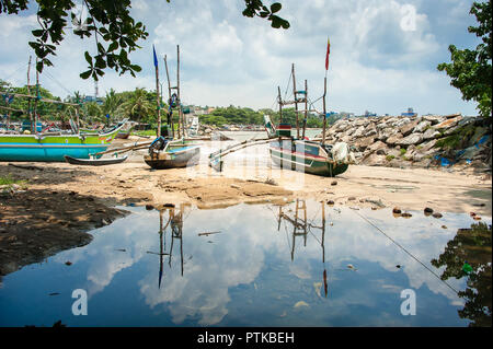 Traditional, painted, wooden fishing boats in the harbour. Colourful Oruwa catamarans sit on a sandy shore with cloudy sky reflections in sea water - Stock Photo