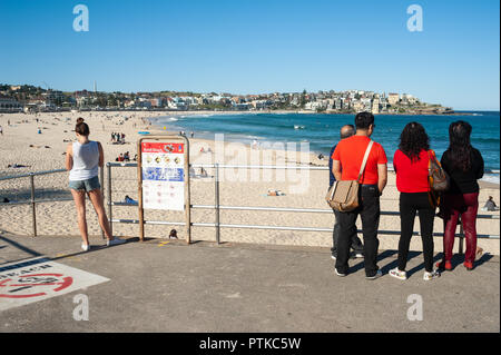 21.09.2018, Sydney, New South Wales, Australia - Tourists are seen standing at an entrance to Sydney's famous Bondi Beach looking at the sea. - Stock Photo