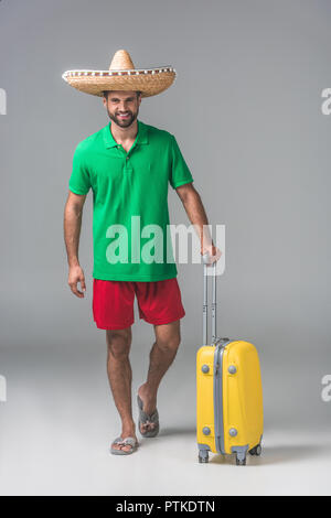 smiling traveler in mexican sombrero standing with suitcase on grey - Stock Photo