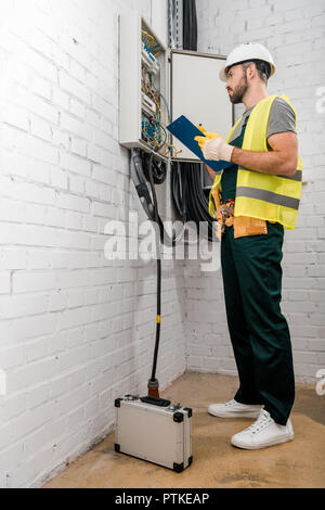 low angle view of handsome electrician holding clipboard and checking electrical box in corridor - Stock Photo