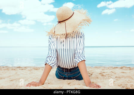 rear view of woman in straw hat relaxing on sandy beach - Stock Photo
