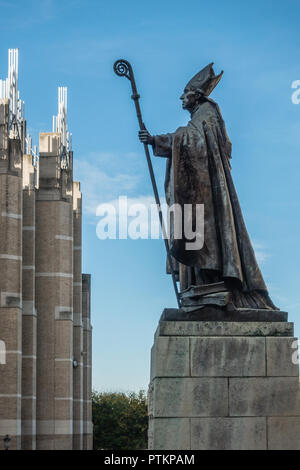 Brussels, Belgium - September 26, 2018: Bronze statue of Catholic Cardinal Mercier on stone pedestal against blue sky looking at office building. - Stock Photo