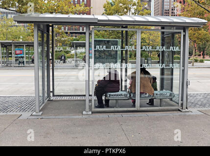Women wait in a public bus shelter on public square in downtown Cleveland, Ohio, USA. - Stock Photo