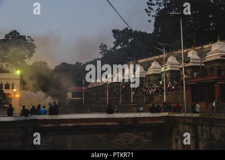 Kathmandu,Nepal - Oct 8,2018:Hindu cremation rituals at the banks of Bagmati river at Pashupatinath Temple premises Aryaghat , Kathmandu. - Stock Photo