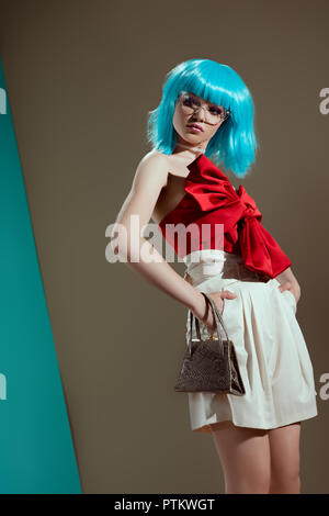 low angle view of beautiful female model in blue wig standing with hands on waist in studio - Stock Photo