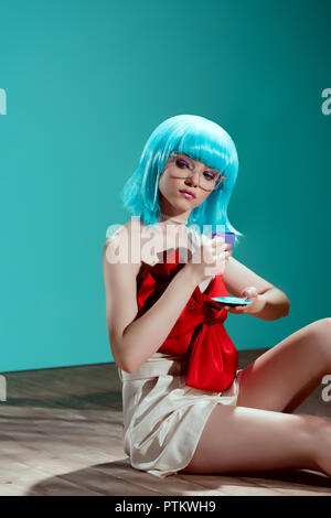 beautiful young woman in blue wig holding toy cup and sitting on floor