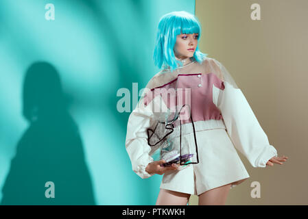 beautiful stylish young woman in blue wig holding transparent cosmetic bag and looking away