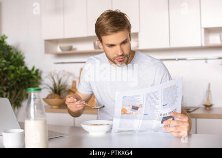 handsome young man eating flakes on breakfast and reading newspaper - Stock Photo