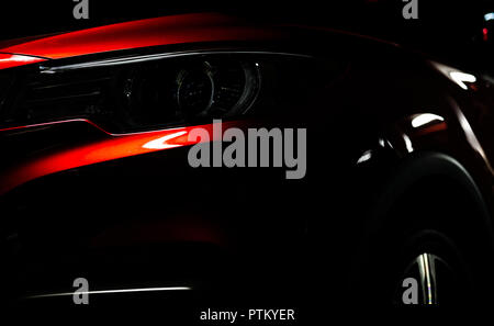 Closeup headlight of shiny red luxury SUV compact car. Elegant electric car technology and business concept. Hybrid auto and automotive concept. Car p - Stock Photo