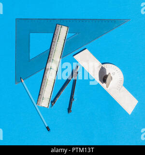 Geometry set with compass, rulers, pencil and protractor on blue background - top view - Stock Photo
