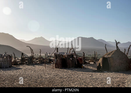 A Himba village with traditional mud huts in the remote province of Kaokaland near to the town of Purros in Namibia. - Stock Photo