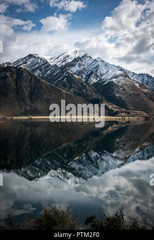 Snow covered mountains near Ben Lomond reflect in the mirror like Moke Lake near Queenstown in New Zealand. - Stock Photo