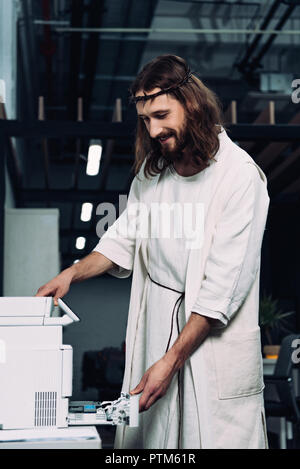 happy Jesus in crown of thorns and robe using copy machine in modern office - Stock Photo
