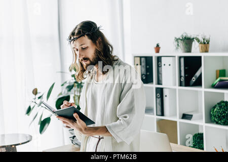 serious Jesus in crown of thorns and robe writing in textbook near working table in modern office - Stock Photo